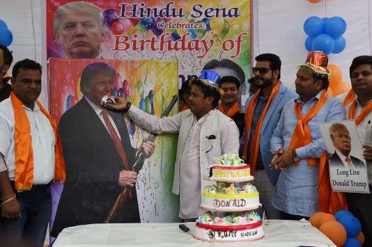 Donald Trump est né le 14 juin 1946. A New Delhi, en Inde, des membres de l'extrême droite fêtent son anniversaire avec un gâteau est une affiche du candidat tenant un fusil.