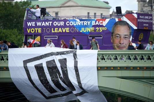 Les partisans du maintien du Royaume-Uni dans l'UE déploient une banderole tandis qu'unbus avec le visage deNigel Farage (UKIP) exhorte les électeurs à quitter l'UE, à Londres le 15 Juin 2016.