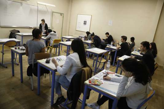 A teacher monitors (Rear L) as High school students start the test of philosophy as they take the baccalaureat exam (high school graduation exam) at the Charlemagne High School (Lycee Charlemagne) in Paris on June 15, 2016. Students across France are registered to take their written baccalaureat exams, starting today with the philosophy test. / AFP / FRANCOIS GUILLOT