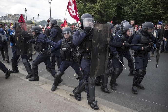 Des policiers pris à parti par des manifestants tentent de s'extirper de la foule, le 14 juin, sur l'esplanade des Invalides à Paris, lors de la manifestation contre la loi travail.