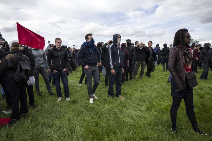 Des personnes regardent la police se mettre en position devant eux, le 14 juin sur l'Esplanade des Invalides à Paris, lors de la manifestation contre la loi Travail.