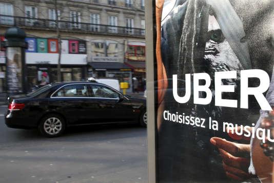 Un taxi passe devant un pub pour les véhicules de tourisme avec chauffeur Uber, à Paris, le 11 mars 2016.
