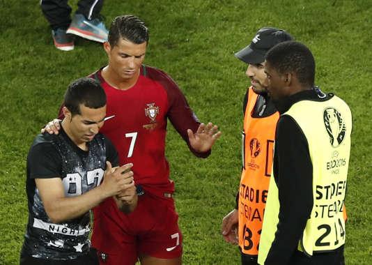 Cristiano Ronaldo fait un geste à des stadiers, au terme de la rencontre entre l'Autriche et le Portugal, alors qu'un supporteur est entré sur la pelouse pour prendre une photo avec le joueur.