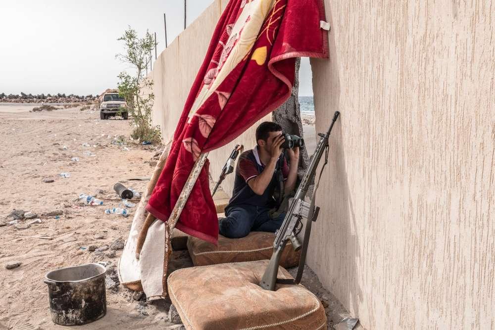 A couvert, un soldat misrati observe les mouvements des combattants de l'EI, le 19 juin.