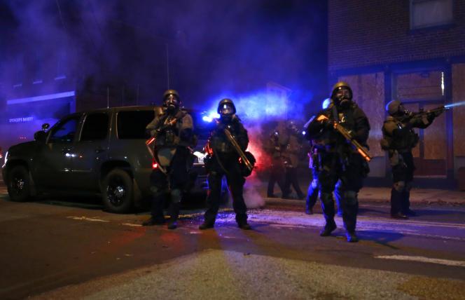 Des policiers équipés de masque à gaz, lors d'une série d'émeutes à Ferguson, le 25 novembre 2014.