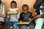 """A refugee boy and his mother from Nigeria read books during a first event of the three-year program """"reading start for refugee children"""" in the refugee camp """"Bayernkaserne"""" in Munich, southern Germany, on March 21, 2016. During the program which starts on behalf of the German Federal Ministry of Education and Research, refugee children up to five year receive a reading start set with an age-appropriate book. / AFP PHOTO / CHRISTOF STACHE"""