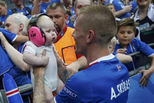 Le joueur islandais Ari Skulason célèbre la qualification avec un jeune supporteur, mercredi 22 juin.