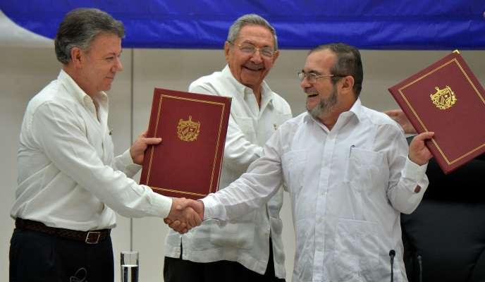 Le président colombien, Juan Manuel Santos (à gauche), et Timoleon Jimenez, alias «Timochenko», le chef de la guérilla des FARC (à droite), échangent une poignée de main sous le regard du président cubain Raul Castro, le 23 juin, à La Havane.