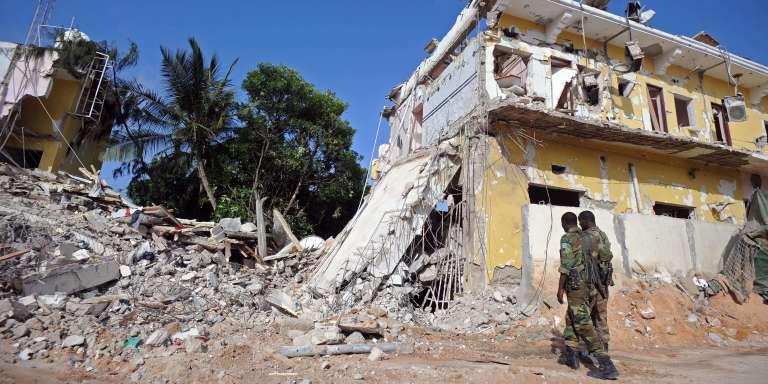 Des soldats somaliens montent la garde, le 26 juin 2016, devant les décombres d'un hôtel détruit par un attentat à Mogadiscio, la veille.Revendiqué par les militants Shebab, il a fait 11 morts.