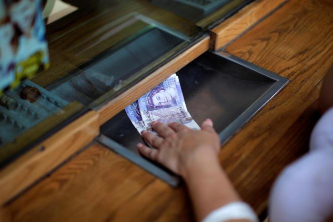 Une femme échange des livres sterling contre des euros, à Gibraltar le 24 juin.
