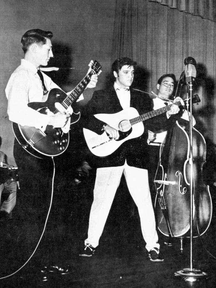 Elvis Presley sur scène en 1957, entouré du guitariste Scotty Moore (gauche) et du contrebassiste Bill Black (droite).