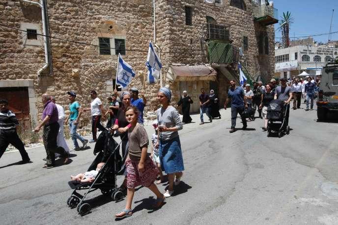 Des colons israéliens protégés par des soldats et policiers reviennent de leur prière du vendredi sur la tombe du patriarche dans les rues de Hébron le 1er juilet 2016.