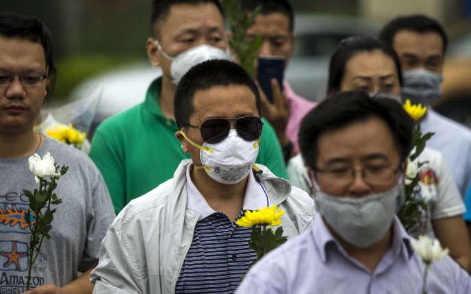 Les résidents de Tianjin portent des fleurs après l'explosion d'un entrepôt de produits chimiques, le 18 août 2015, en Chine.