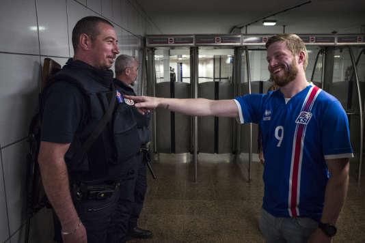 Un policier affichant le drapeau de l'Islande en signe de bienvenue est accueilli chaleureusement par les supporteurs islandais, le 3 juillet 2016, à la sortie de métro du Stade de France à Saint-Denis, peu avant le début du match France-Islande comptant pour les huitièmes de finale de l'Euro.