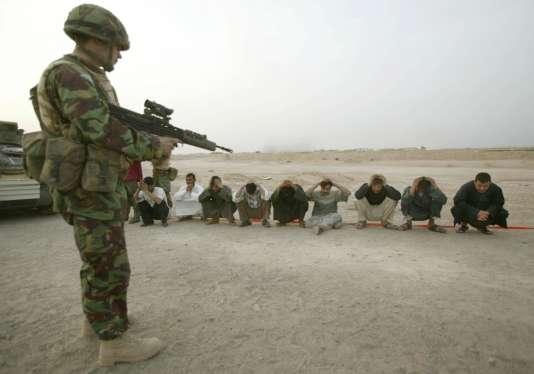 Un soldat britannique surveille des citoyens irakiens près de Bassorah, le 24 mars 2003.