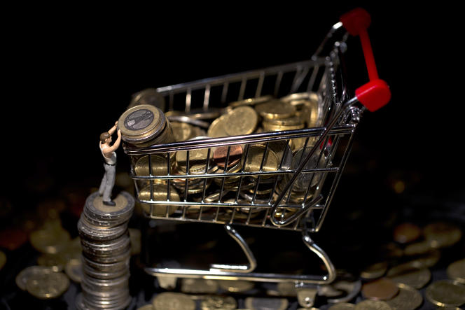 This illustration photo taken on December 25, 2012, in Paris, shows a figurine next to a miniature toy shopping cart filled with coins. AFP PHOTO / JOEL SAGET / AFP PHOTO / JOEL SAGET