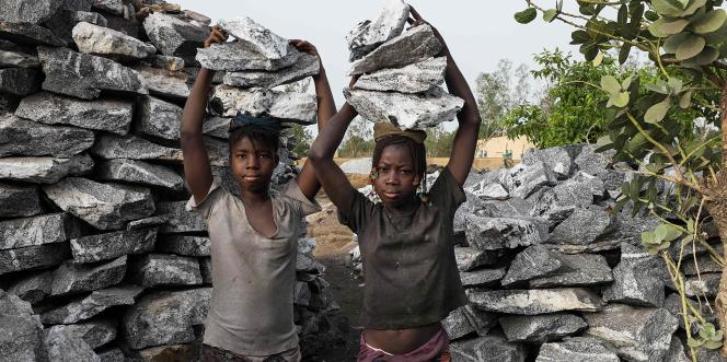 Deux jeunes filles posant avec du granit sur leur tête dans la carrière de Pissy, à l'ouest de Ouagadougou, le 10 juin 2016.