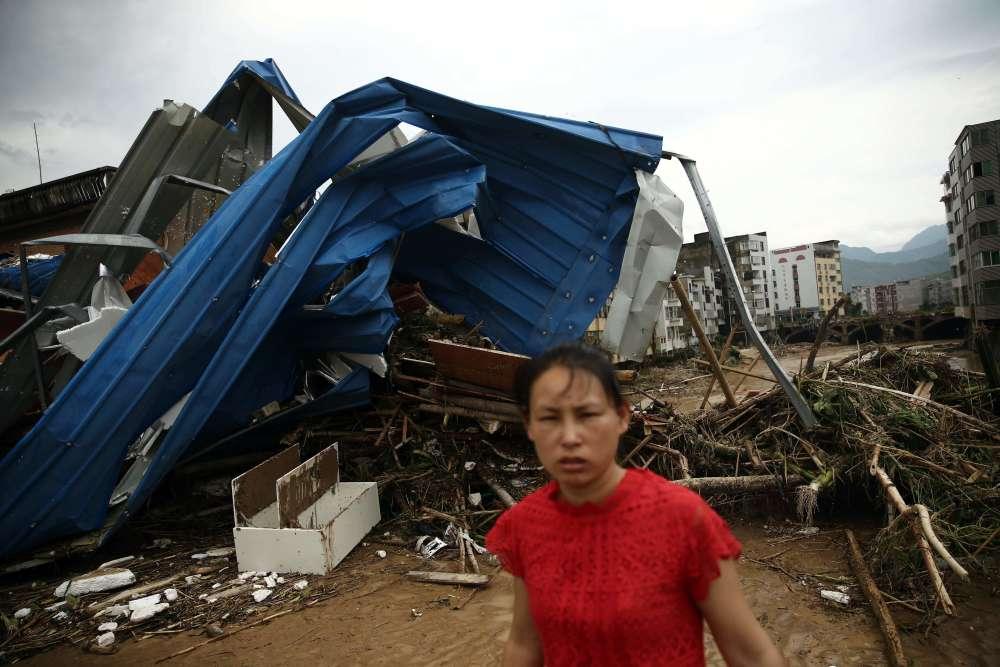 Au lendemain de la tempête tropicale qui a secoué la région, une femme progresse à travers les ruines. Au cours du week-end, l'électricité a été coupée pour des centaines de milliers d'habitants du Fujian, tandis que les transports ont été sévèrement perturbés. Cinq aéroports ont été fermés selon le quotidien «Global Times».