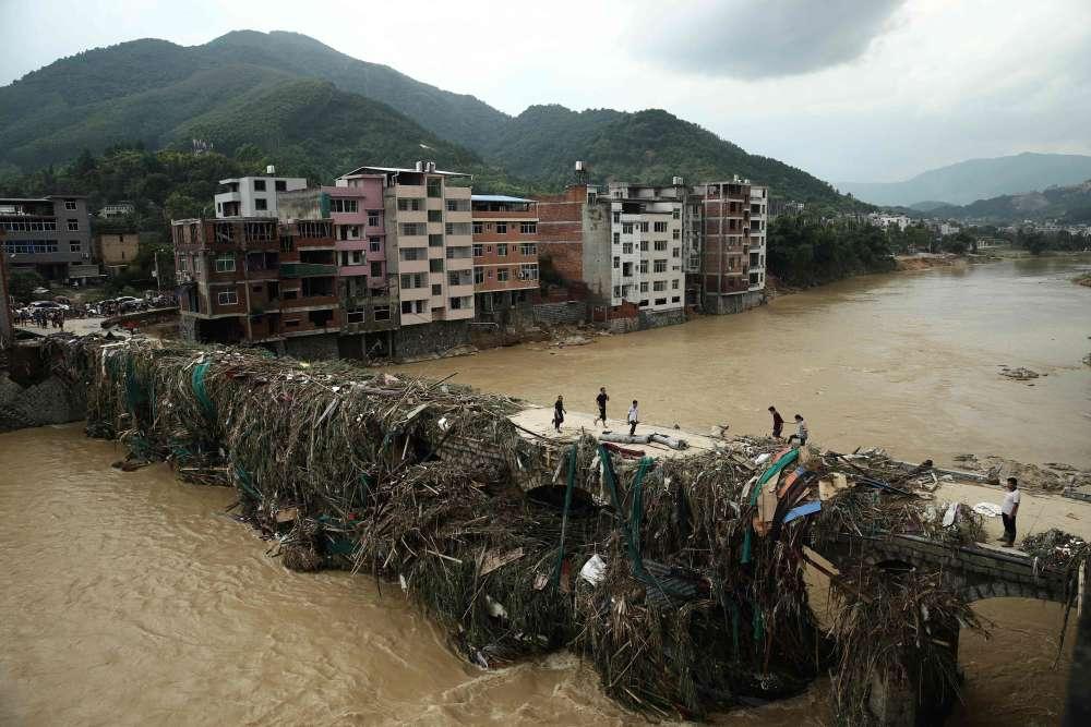 Bandong, province de Fujian (est de la Chine), le 10 juillet. Des habitants traversent un pont couvert de débris suite au passage, la veille, du typhon Nepartak. Malgré la baisse de son intensité, la tempête a entraîné des dégats matériels majeurs.Plus de 200 000 résidents dans dix villes chinoises ont dû être temporairement relogés, tandis que plus de 1 900 logements ont été détruits.