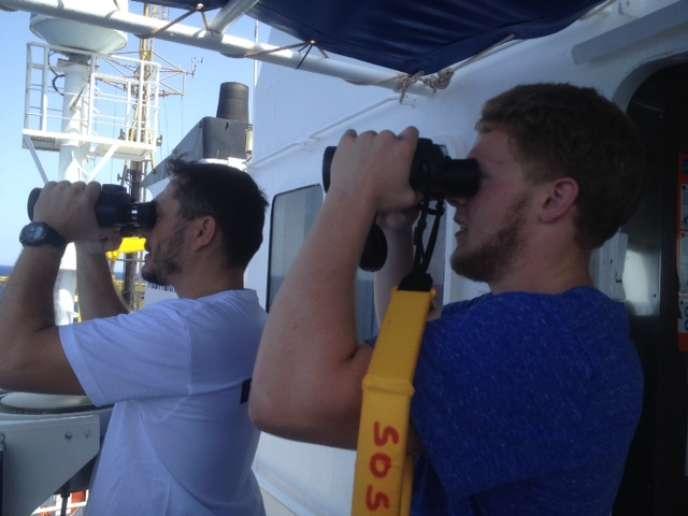 L'officier et l'étudiant volontaire scrutent la mer.