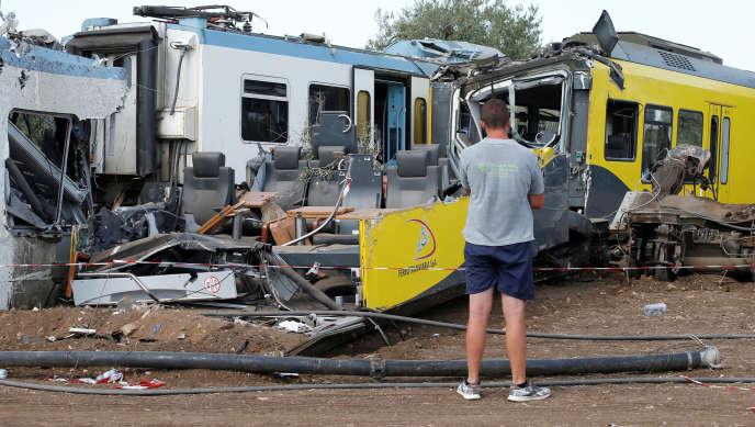 Un homme regarde les carcasses des trains qui sont entrés en collision, mardi 12 juillet 2016, dans le sud de l'Italie.