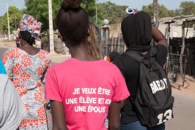 Une membre du club de jeunes filles du quartier de Sintian avec un tee-shirt «Je veux être une élève et non une épouse».