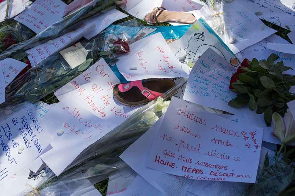 Sur la promenade des Anglais, des jouets d'enfants et des peluches ont été déposés parmi les fleurs, devant le dessin d'un doigt d'honneur en bleu blanc rouge.