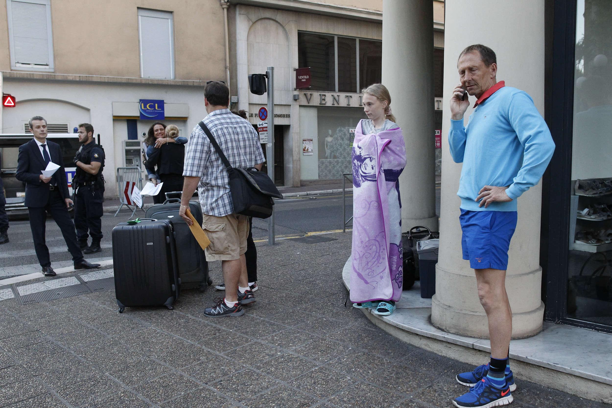 Des touristes,aidés par le personnel d'un hotel rue du Congres, attendent un taxi alors quela rue estbloquée.