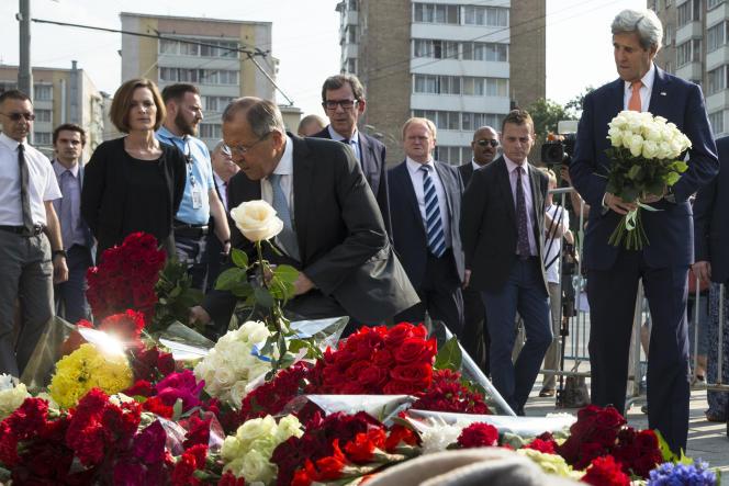 Le ministre russe des affaires étrangères, Sergueï Lavrov, et le secrétaire d'Etat américain, John Kerry (à droite), déposent des fleurs devant l'ambassade de France à Moscou en hommage aux victimes de l'attaque de Nice, le 15 juillet