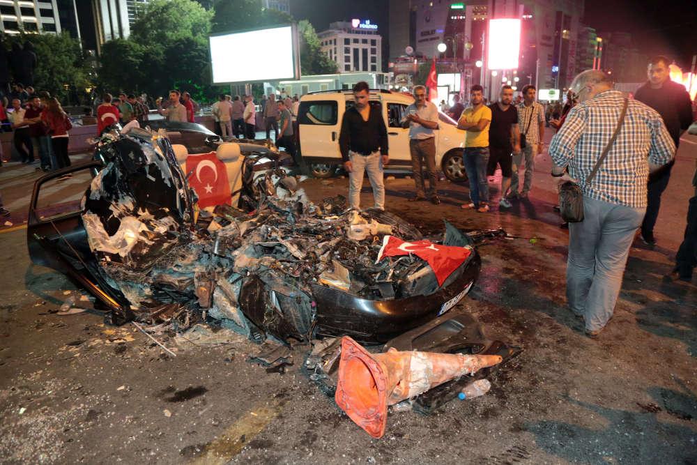 Des gens regardent une voiture qui a été écrasée par un tank au parc Kizilay d'Ankara.