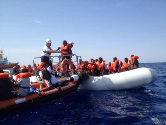 Mathias Menge accueille un migrant que Bertrand Thiébault a hissé à bord