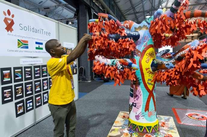 Un délégué accroche des rubans symboliques de la lutte contre le sida, à Durban (Afrique du Sud), le 19 juillet.