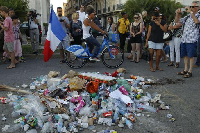Devant les détritus marquant l'endroit où le meurtrier a été abattu, sur laPromenade des Anglais, à Nice le 18 juillet.