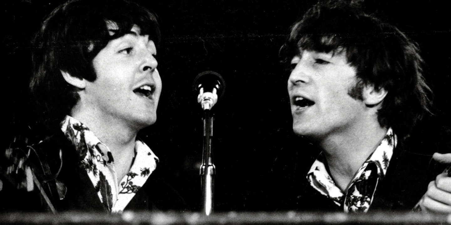 John Lennon and Paul McCartney of The Beatles share a microphone during the last concert on their final tour at Candlestick Park, San Francisco, California, August 29, 1966. (Photo by Koh Hasebe/Shinko Music/Getty Images)
