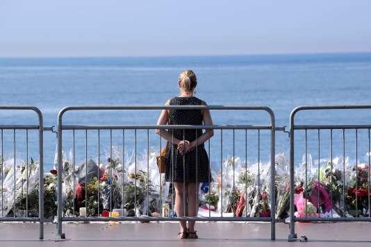 Une femme se receuille devant les fleurs déposées en hommage aux personnes tuées dans l'attentat de Nice, le 14 juillet.