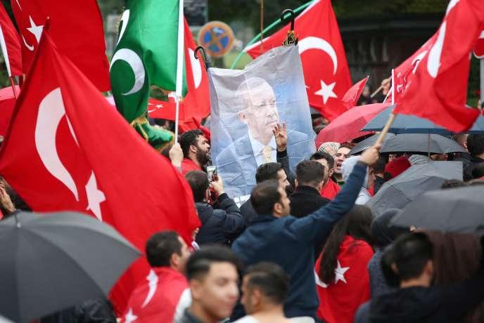Des membres de la communauté turque à Hambourg en Allemagne, le 16 juillet 2016, brandissent des drapeaux et le portrait du président Erdogan face au consulat, en guise de protestation contre le coup d'Etat militaire.
