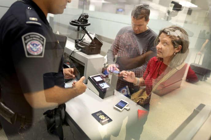 Contrôle par un officier des services des douanes de passagers arrivant de l'étranger à l'aéroport de Miami en 2015.
