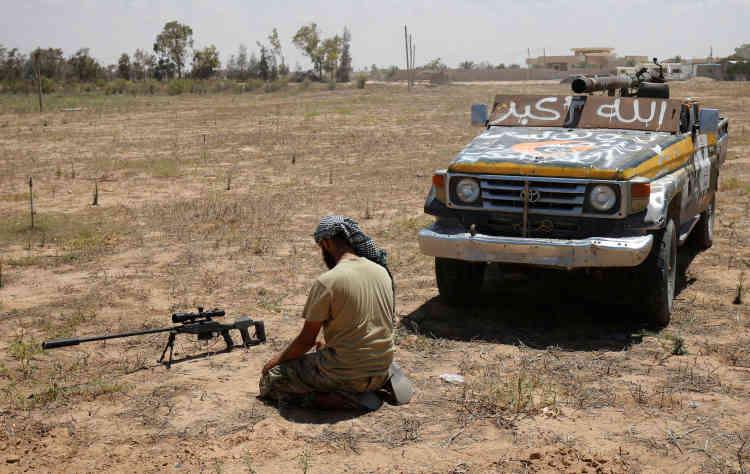 Un tireur des forces gouvernementales prie devant son fusil de précision, à Syrte, le 21 juillet.