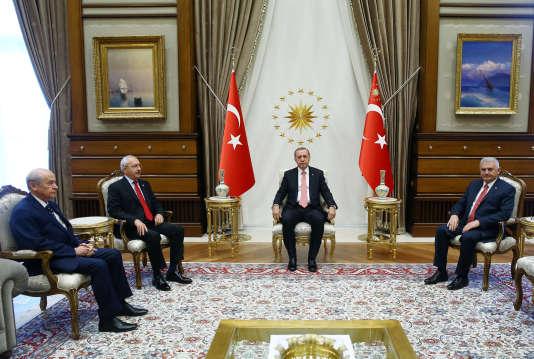 Le président turc, Recep Tayyip Erdogan, avec le premier ministre, Binali Yildirim (à droite), le chef du Parti républicain du peuple (CHP), Kemal Kiliçdaroglu, et celui du Parti d'action nationaliste (MHP), Devlet Bahçeli, à Ankara, lundi 25 juillet 2016.