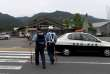 Police officers walk towards the Tsukui Yamayuri En care centre (in background) where a knife-wielding man went on a rampage in the city of Sagamihara, Kanagawa prefecture, some 50 kms (30 miles) west of Tokyo on July 26, 2016. At least 19 people were killed when the knife-wielding man went on a rampage at the care centre for the mentally disabled in Japan early on July 26, a fire official said. / AFP / TOSHIFUMI KITAMURA