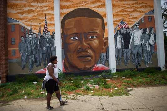 Une femme passe devant un mur sur lequel a été peint le visage de Freddie Gray, jeune Noir mort dans un fourgon de la police à Baltimore, aux Etats-Unis.