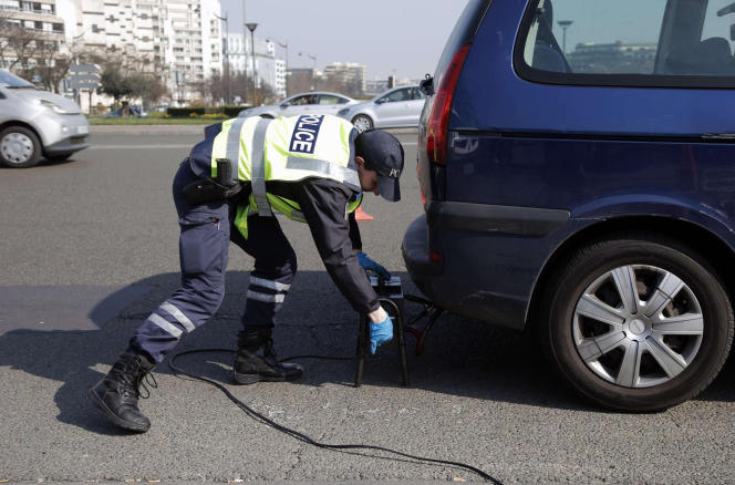 Les policiers contrôlent des voitures à l'entrée de Paris, le 23 mars 2015, lors d'un pic de pollution ayant entraîné une mesure de circulation alternée.