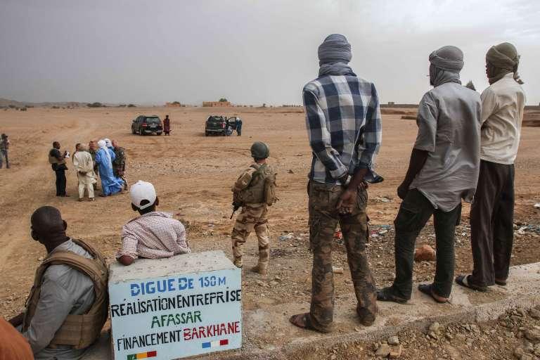 Des habitants observent l'horizon qui se couvre, perchés sur la digue en cours de finition à Amachache.