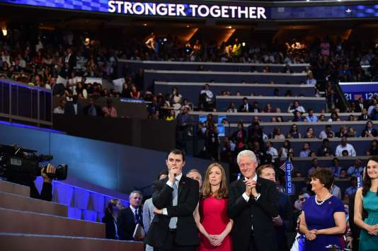 L'ancien président des Etats-UnisBill Clinton, sa fille, Chelsea Clinton, et le mari de celle-ci, Marc Mezvinsky, regardent la candidate démocrate, Hillary Clinton, prononcer son discours d'investiture, jeudi 28 juillet 2016 à Philadelphie.