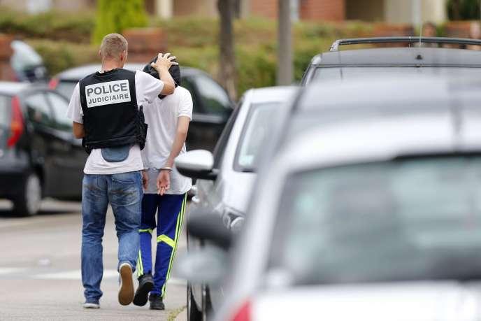 Un policier arrête un homme à Saint-Etienne-du-Rouvray, le 26 juillet, après l'attentat dans l'église de cette commune de Seine-Maritime où a été assassiné le père Jacques Hamel.