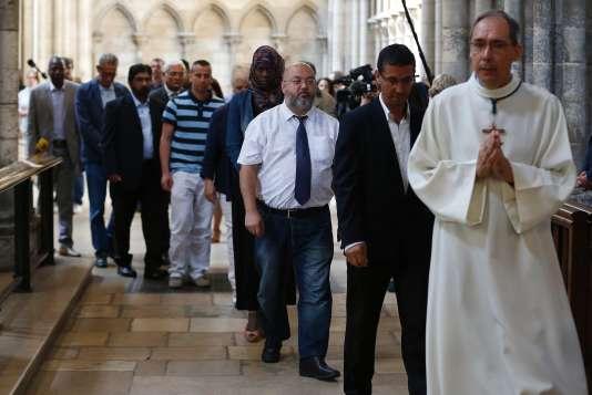 Des fidèles musulmans marchent derrière un prêtre, dimanche 31 juillet lors d'une messe célébrée en hommage au père Jacques Hamel.
