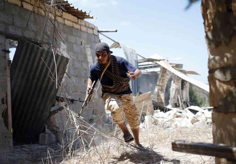 Un combattant des forces pro gouvenementales court pour s'abriter des tirs de l'EI dasn les rues de Syrte le 31 juillet.