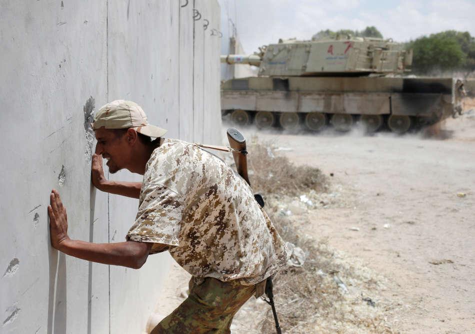Un combattant surveille un tir de RPG sous le couvert d'un mur de sirte le 31 juillet.