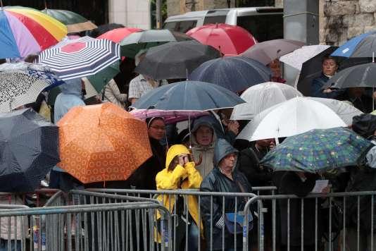 Sous la pluie, des gens attendent devant la cathédrale de Rouen, où se déroulent les obsèques du Père Jacques Hamel, mardi 2 août.