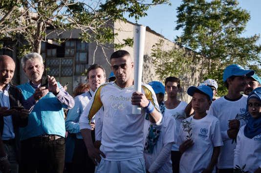 Ibrahim Al-Hussein, réfugié syrien de 27 ans, porte la flamme olympique dans le camp d'Elaionas, dans la banlieue d'Athènes, le 26 avril. Le jeune hommedevrait s'envoler le 25 août pour Rio afin de participer aux Jeux paralympiques avec l'équipe grecque de natation. Mais il attend encore son visa.
